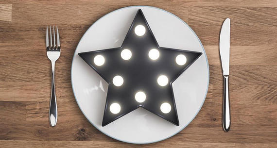 Dinner setting with lighted star on a wooden background.