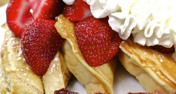 French toast with strawberries and powdered sugar finished with whipped cream.