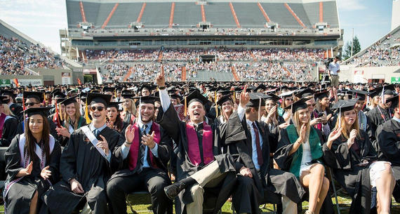 Virginia Tech Graduates seated and cheering during Commencement at Lane Stadium
