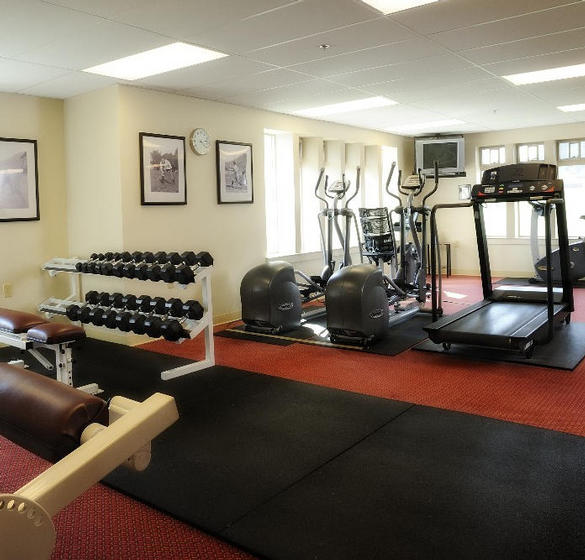 Onsite fitness room with two elliptical machines, a treadmill machine, and hand weight station.