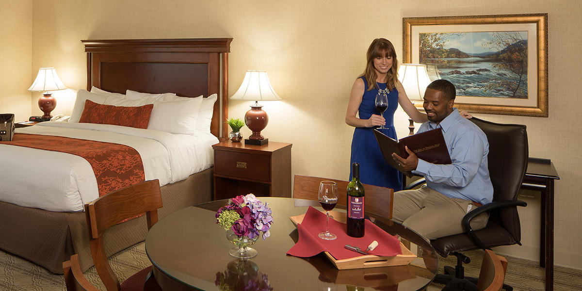 Couple in deluxe king guest room looking at room service menu