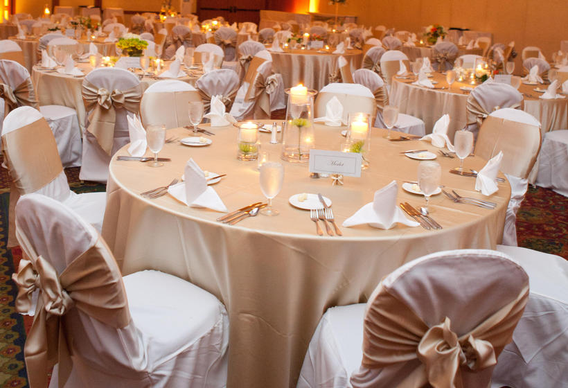 Reception tables in ballroom decorated with champagne colored linens and smal centerpieces