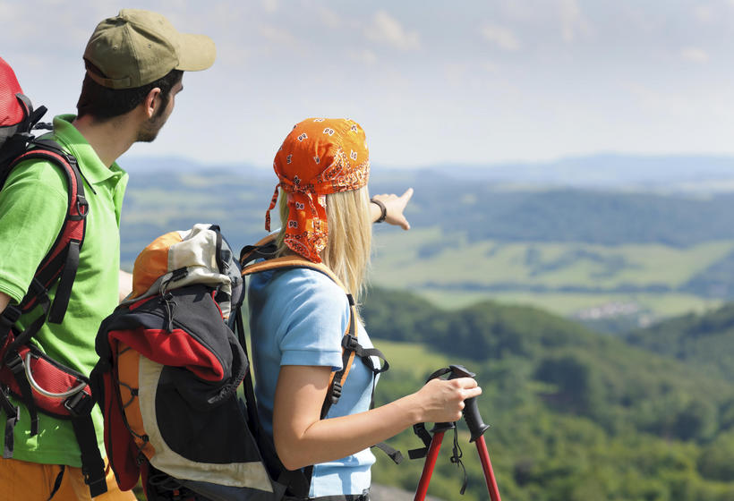 Man and Woman with hiking gear overlooking a valley